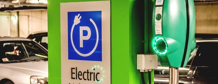 Kuva vihreästä sähköautojen latauspisteestä parkkihallissa. Taustalla vaaleanharmaa ja musta auto.