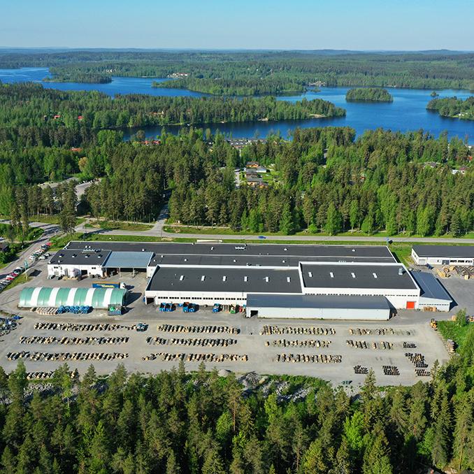 Keuruun tehtaan ilmakuva, pihalla siistejä kelarivejä. Taustalla järvimaisema.