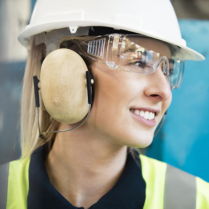 Naistyöntekijä turvaliivi, kypärä, suojalasit ja kuulosuojaimet päällä.