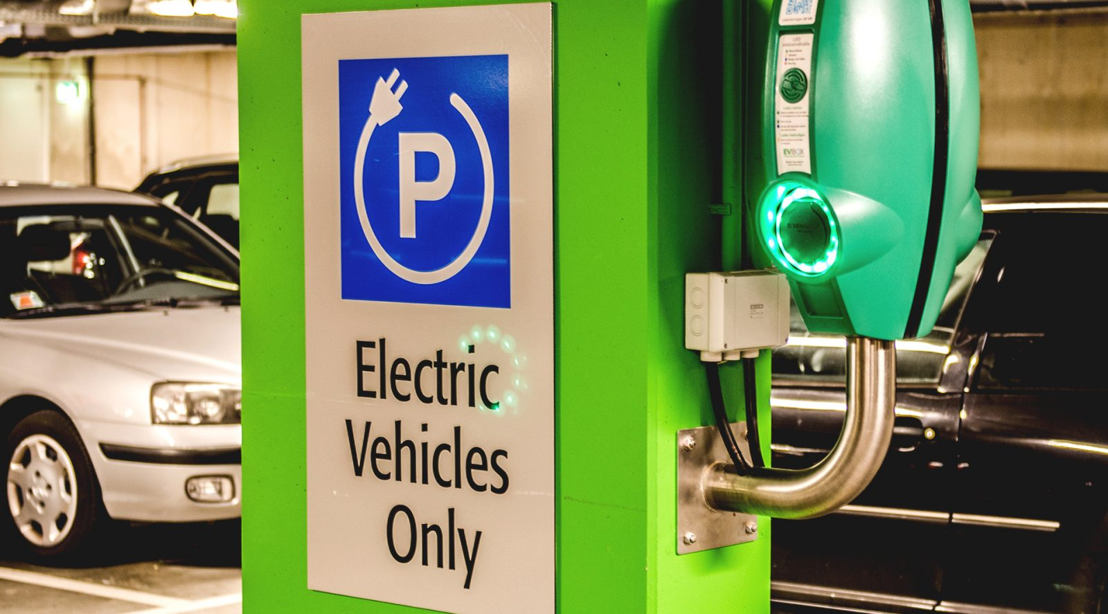 Kuva vihreästä sähköautojen latauspisteestä parkkihallissa. Taustalla musta ja valkoinen auto.